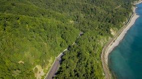 flyg- foto för materiel 4K av bilkörning längs den slingriga vägen för bergpasserande till och med skogen i Sochi, Ryssland Arkivbilder