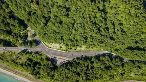 flyg- foto för materiel 4K av bilkörning längs den slingriga vägen för bergpasserande till och med skogen i Sochi, Ryssland Arkivbild