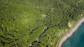 flyg- foto för materiel 4K av bilkörning längs den slingriga vägen för bergpasserande till och med skogen i Sochi, Ryssland Royaltyfria Foton