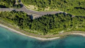 flyg- foto för materiel 4K av bilkörning längs den slingriga vägen för bergpasserande till och med skogen i Sochi, Ryssland Arkivfoto