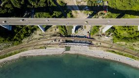 flyg- foto för materiel 4K av bilkörning längs den slingriga vägen för bergpasserande till och med skogen i Sochi, Ryssland Fotografering för Bildbyråer