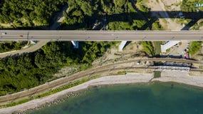 flyg- foto för materiel 4K av bilkörning längs den slingriga vägen för bergpasserande till och med skogen i Sochi, Ryssland Arkivfoton