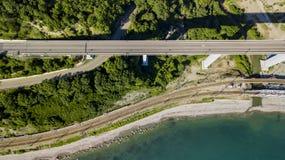 flyg- foto för materiel 4K av bilkörning längs den slingriga vägen för bergpasserande till och med skogen i Sochi, Ryssland Royaltyfri Fotografi