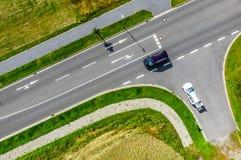 Flyg- fotografi av föreningspunkten av en väg in i en stor väg som markeras med vit teckning för rak körning och att vända, med a royaltyfria foton