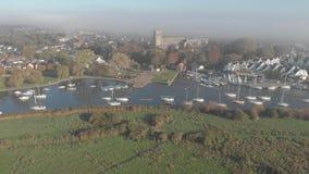 Flyg- framåt längd i fot räknat av en dimmig Christchurch UK priorskloster som passerar över floden stock video