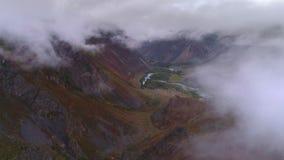 Flyg- längd i fot räknat av en molnig bergdal Flyg över arkivfilmer