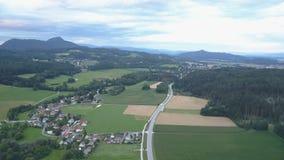 Flyg- längd i fot räknat av en by och en väg mellan gräsplanfält och skogar på solnedgång Berg på horisont arkivfilmer