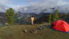 Flyg- längd i fot räknat av ett mananseende nära ett tält framme av bergdalen 4K stock video