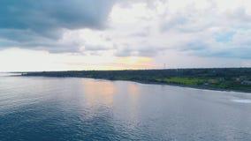 Flyg- längd i fot räknat av solnedgången på havsstranden med azurer bevattnar, slösar molnig himmel på Bali lager videofilmer