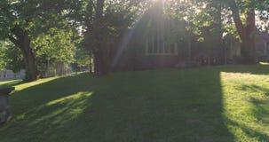 Flyg- låg flygsikt av gravstenar i en liten kyrkogård bak en kyrka stock video