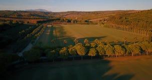 Flyg- flyg, låg höjd, över kullar och polofält på solnedgången lager videofilmer