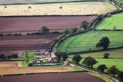Flyg- lantgårdbyggnader och fält Arkivfoton