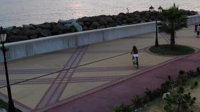 Flyg- flyg med surret DJI över härlig ung sexig brunettflicka med cykeln på en bakgrund av havssolnedgången arkivfilmer