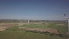 Flyg nära en vindkraftstation i dagen på våren Roterande blad av energigeneratorer Ekologiskt rent electricit lager videofilmer