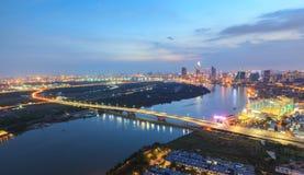 Flyg- nattsikt av färgrik och vibrerande cityscape av centret i Ho Chi Minh City med den Thu Thiem bron