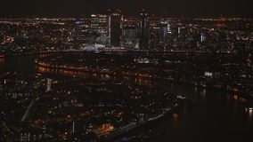 Flyg- nattsikt av upplysta skyskrapor på Canary Wharf det finansiella området och östlig del av London bredvid flodThemsen stock video