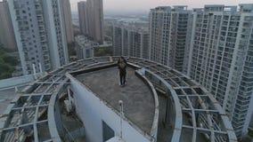 Flyg- orbital skott av att krama och att kyssa par på taköverkanten av modern lägenhetbyggnad på solnedgången stock video