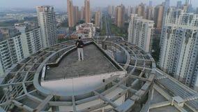 Flyg- orbital skott av att krama par på taköverkanten av modern lägenhetbyggnad på solnedgången lager videofilmer