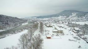 Flyg- flyg ovanför floden i vinter flod som slingrar till och med att bedöva snöig vinterlandskap lager videofilmer