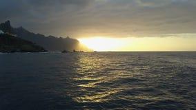 Flyg ovanför havvågor som vänder mot härlig solnedgång och berg på horisont Flyg- surrskott av den härliga solnedgången på arkivfilmer