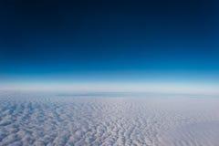 Flyg ovanför molnen med en sikt av himlen royaltyfri foto