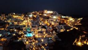 Flyg- panorama av den Oia staden på natten, Santorini lager videofilmer
