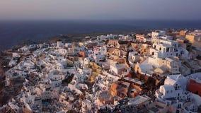 Flyg- panorama av den Oia staden på solnedgången, Santorini stock video