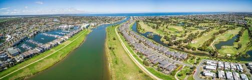 Flyg- panorama av den Patterson Lakes förort och floden med golfcl Royaltyfria Bilder