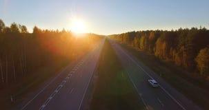 Flyg- panorama- av en huvudväg med trafik längs blandade ädelträn och barrträdskog på solnedgången lager videofilmer