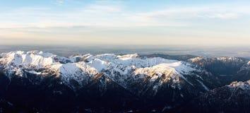 Flyg- panorama av snöig bergblast i solnedgång arkivbilder