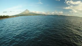 Flyg- panorama av staden av Legaspi i morgonen på gryning Mot bakgrunden av den Mayon vulkan Hamnstad med lager videofilmer