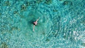 Flyg- panorama på dans för ung kvinna och vända omkring i det blåa havet arkivfilmer