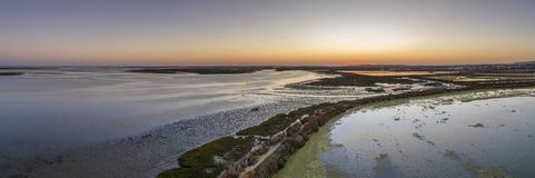 Flyg- panorama- seascapesikt för solnedgång av öppningen Olhao för salt träsk Arkivbild
