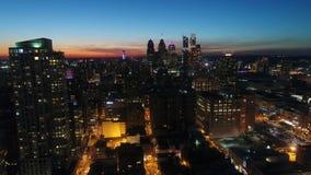 Flyg- panoramaflyg för fantastiskt surr 4k i orange solnedgångaftonhimmel över storstaden i nattljusPhiladelphia cityscape stock video