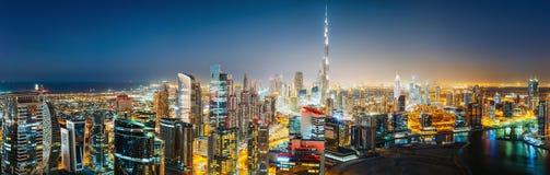 Flyg- panoramautsikt av en stor futuristisk stad vid natt AFFÄRSFJÄRD, DUBAI, UAE Fotografering för Bildbyråer