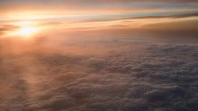 Flyg- resa Flyg på skymning eller gryning Fluga till och med det orange molnet och solen royaltyfri fotografi