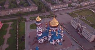 Flyg- flyg runt om ny kyrka i liten stad Kristen tempel och guld- kyrklig kupol på gryning 4K lager videofilmer