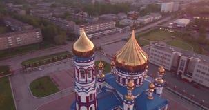 Flyg- flyg runt om ny kyrka i liten stad Kristen tempel och guld- kyrklig kupol på gryning 4K arkivfilmer