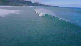 flyg- seascape för surr 4k av surfaren som surfar i den enorma vita skumvågen som plaskar i lugna djupblått havvatten på molnig d lager videofilmer