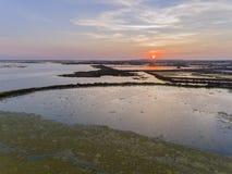 Flyg- seascapesikt för solnedgång av öppningen Olhao för salt träsk Royaltyfria Bilder