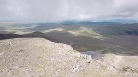 Flyg- sikt av överkanten av berget med många stenar och en snöglaciär i sommaren i bergen av Altaien med stort lager videofilmer