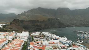 Flyg- sikt av Agaete, Gran Canaria, kanariefågelöar Port i en liten fjärd med dyra yachter, vita hus och a stock video