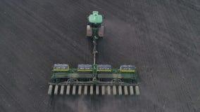 Flyg- sikt av att ploga för vår av fältet med en traktor med en odlare, jordförberedelse vid det jordbruks- bruket stock video
