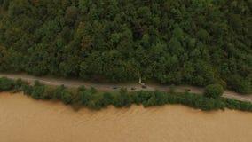 Flyg- sikt av bergfloden med bilar på vägen lager videofilmer