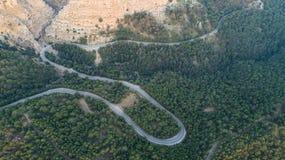 Flyg- sikt av bergkurvvägen Grön skog på solnedgången i sommar i Europa Landskapet med asfaltv?gen, tr?d p? vaggar arkivfoton