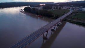 Flyg- sikt av beskickningflodbron på skymning med bilar som pendlar över den stock video