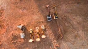 Flyg- sikt av bulldozrar och lastbilar som är klara för nybyggnad Arkivfoto