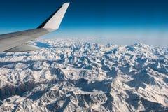 Flyg- sikt av de italienska schweiziska fjällängarna i vinter, med den generiska flygplanvingen Snowcapped bergskedja och glaciär Royaltyfria Bilder