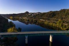 Flyg- sikt av den Belver slotten Castelo de Belver och by med bron över Taguset River i förgrunden, i Portug Fotografering för Bildbyråer