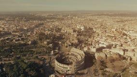 Flyg- sikt av den berömda Colosseum eller Coliseumamfiteatern inom cityscape av Rome, Italien lager videofilmer